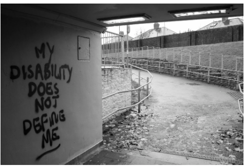 """A black and white photo of a covered place with walls opening  up to an uphill ramp. The wall has text on it that reads """"My disability does not  define me."""""""
